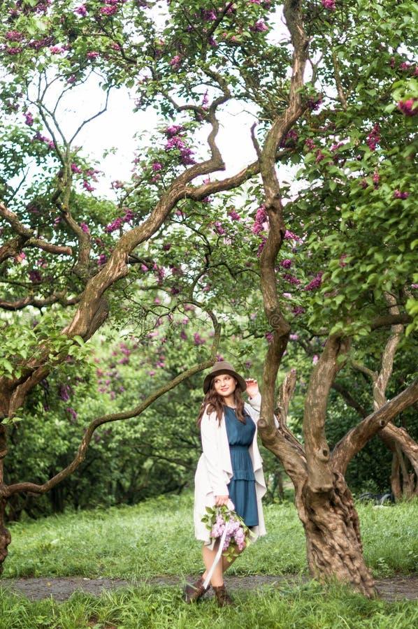 La ragazza felice alla moda ammira il fiore lilla nel giardino fotografie stock