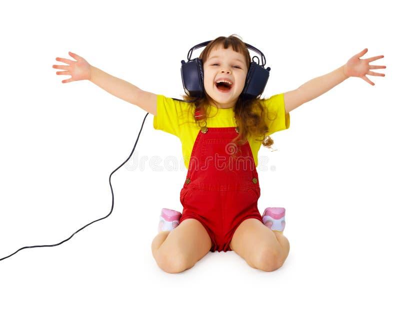 La ragazza felice ascolta musica con le cuffie immagine stock