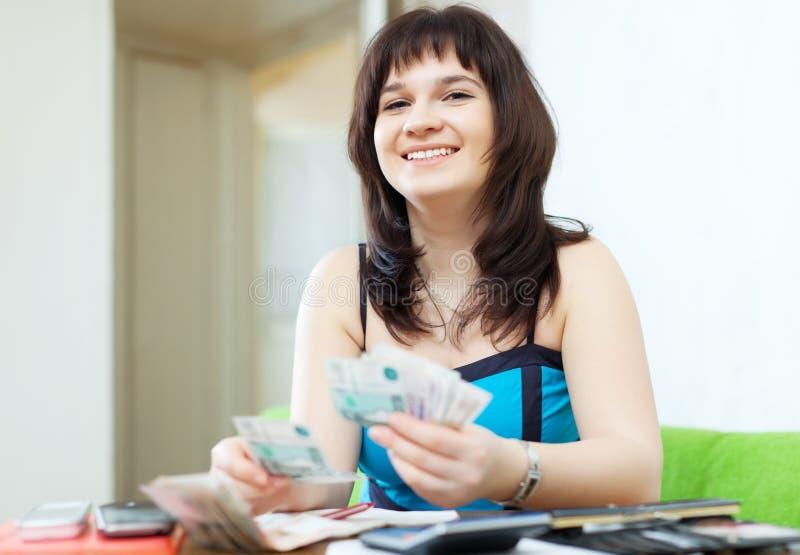 La ragazza felice calcola il bilancio familiare fotografia stock