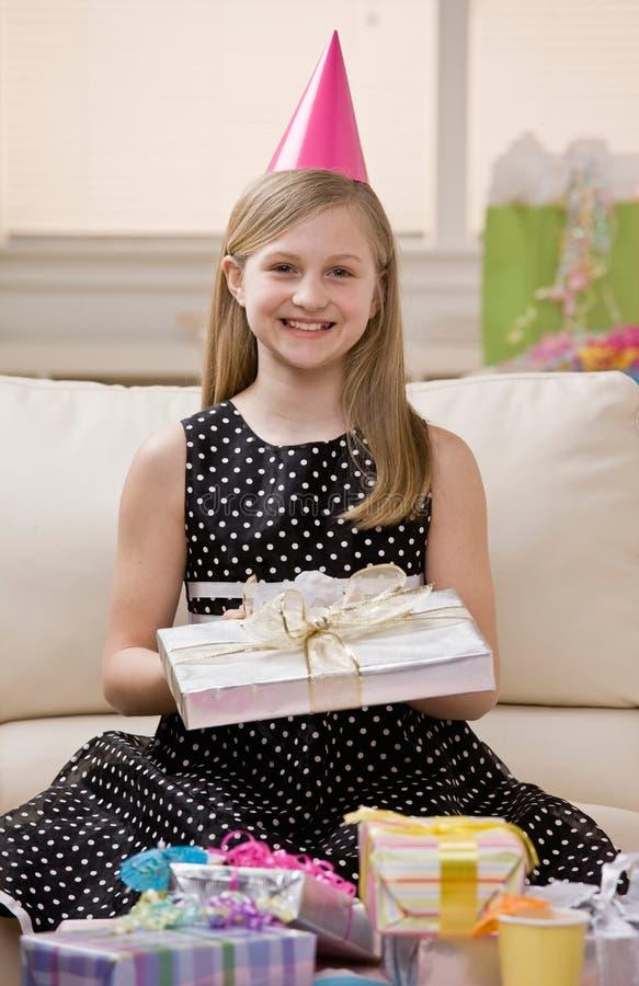 La ragazza felice in cappello del partito apre i regali di compleanno immagine stock libera da diritti