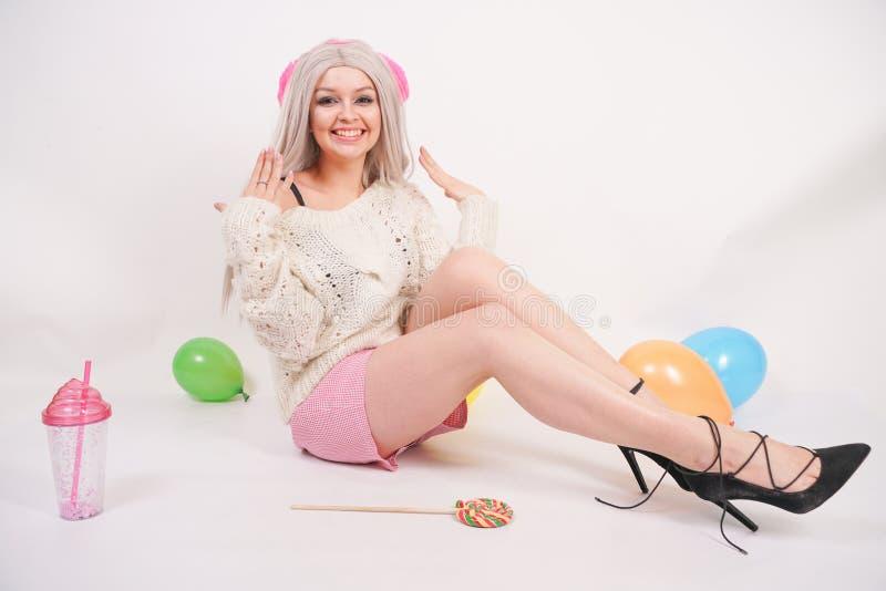 La ragazza felice caucasica bionda sveglia vestita in un maglione tricottato colore latteo e divertente mette, lei si siede sul p fotografia stock