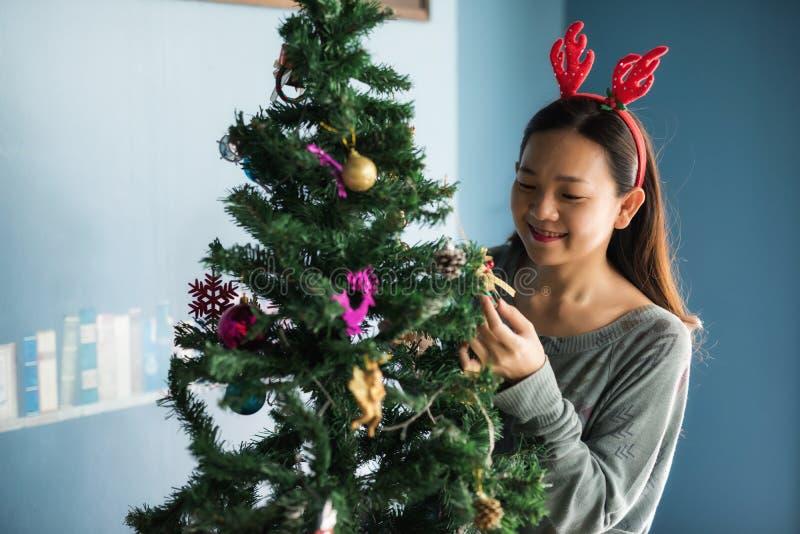 La ragazza felice cinese asiatica con il costume della renna decora i regali sull'albero di natale La donna sveglia attraente cel immagini stock