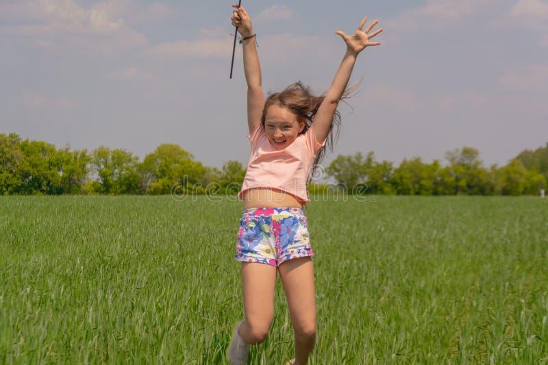 La ragazza felice con capelli lunghi che tengono un giocattolo colorato del mulino a vento in sue mani solleva la suoi mano e sal fotografie stock