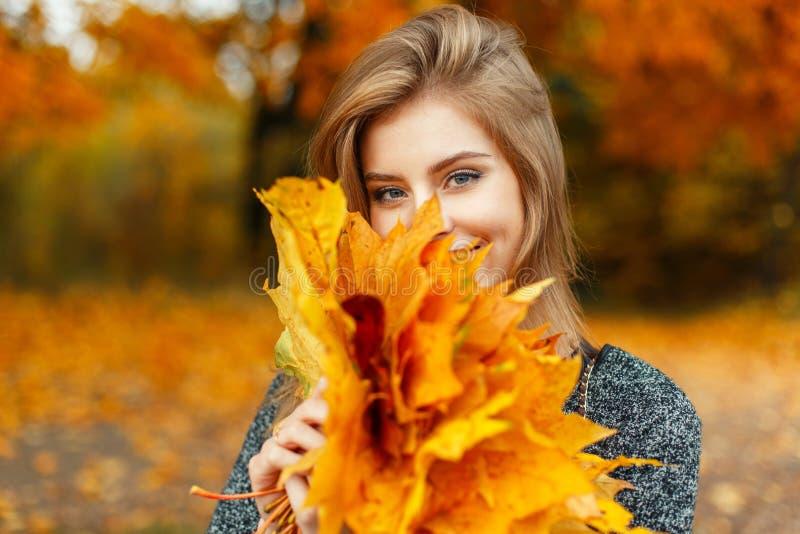 La ragazza felice con giallo di autunno lascia godere del tempo fotografia stock libera da diritti