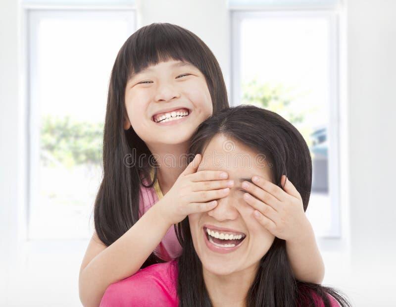 La ragazza felice copre i suoi occhi della madre fotografia stock