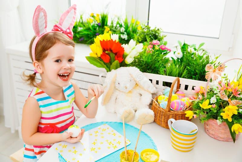 La ragazza felice del bambino dipinge le uova per Pasqua immagini stock