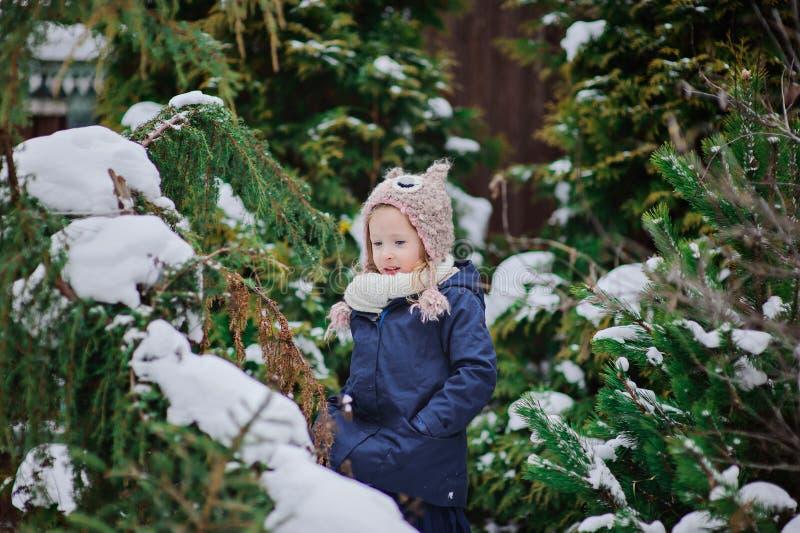 La ragazza felice del bambino gioca nel giardino nevoso dell'inverno fotografie stock libere da diritti