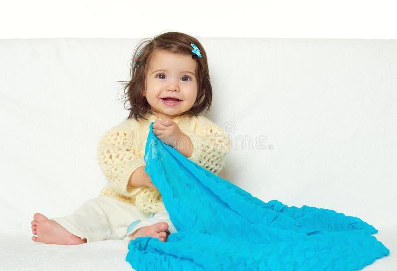 La ragazza felice del piccolo bambino si siede sull'asciugamano bianco, sull'emozione felice e sull'espressione del fronte, giall immagini stock libere da diritti