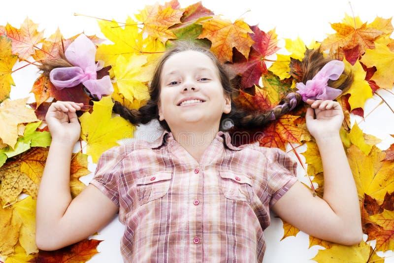 La ragazza felice dell'adolescente risiede nei fogli di acero fotografia stock