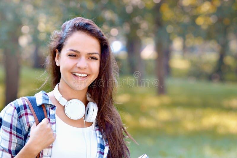 La ragazza felice dello studente con lo zaino e le cuffie sorridono nel parco dell'estate fotografie stock libere da diritti
