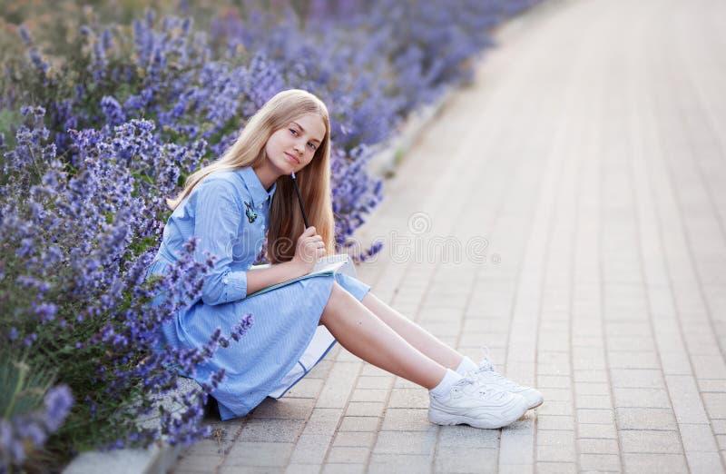 La ragazza felice dello studente con la penna scrive in un taccuino, sedentesi nel parco nei fiori fuori scolara in uno studio bl fotografia stock
