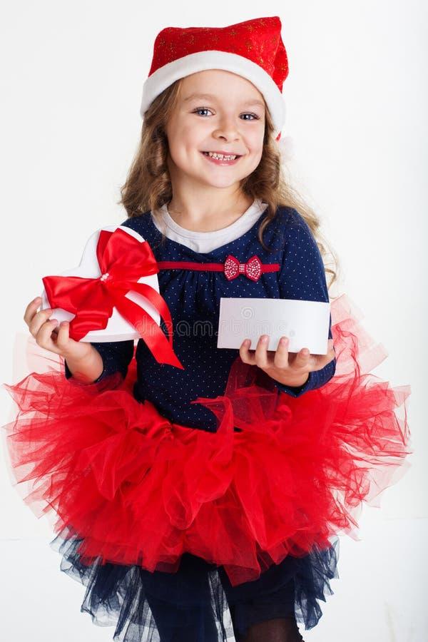 La ragazza felice di Santa sta tenendo il contenitore di regalo fotografia stock libera da diritti