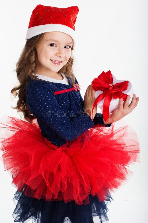 La ragazza felice di Santa sta tenendo il contenitore di regalo con rosso fotografia stock
