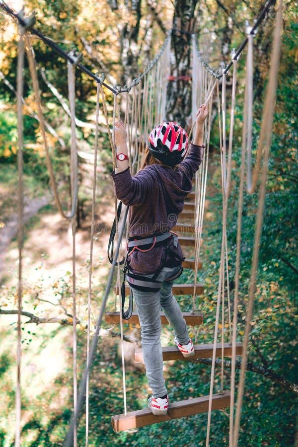 La ragazza felice, donne, ingranaggio rampicante in un parco di avventura è impegnata in arrampicata sulla strada della corda, l' immagine stock