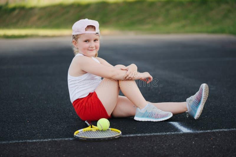 La ragazza felice gioca a tennis sulla corte all'aperto fotografie stock