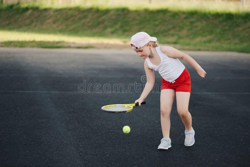 La ragazza felice gioca a tennis sulla corte all'aperto immagine stock