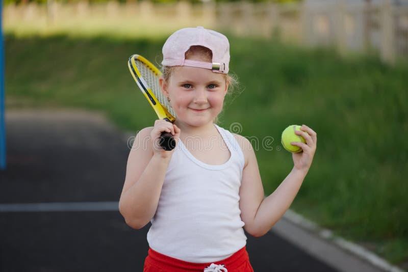 La ragazza felice gioca a tennis sulla corte all'aperto fotografia stock