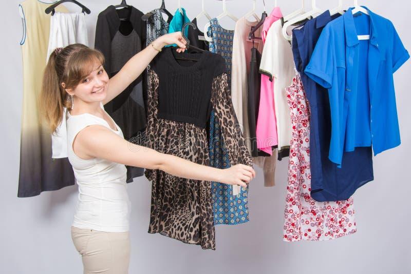 La ragazza felice ha scelto un vestito in guardaroba fotografia stock