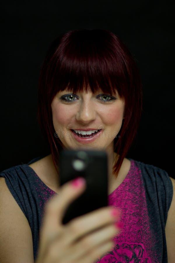 La ragazza felice legge il messaggio di testo sul telefono delle cellule fotografia stock libera da diritti