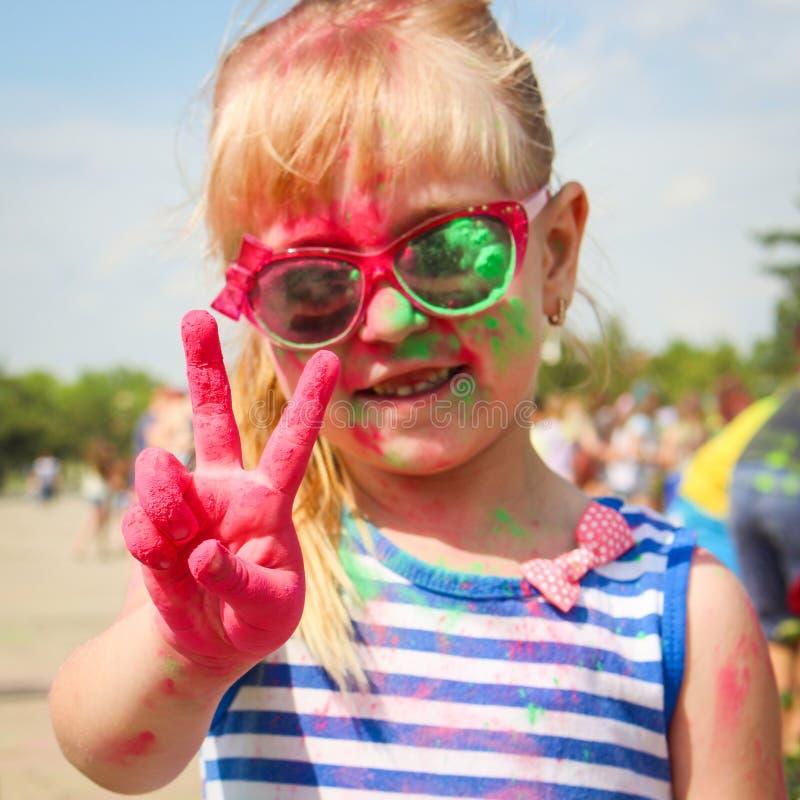La ragazza felice mostra la vittoria del segno con la pittura di holi immagini stock libere da diritti