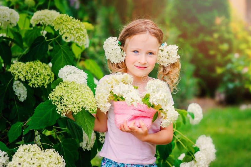 La ragazza felice sveglia del bambino con l'ortensia fiorisce il mazzo nel giardino dell'estate fotografia stock