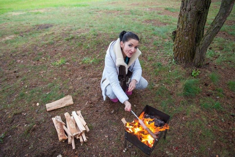 La ragazza frigge le salsiccie in natura Una donna vicino alle salsiccie delle fritture del fuoco nell'alimento delizioso del fuo fotografie stock