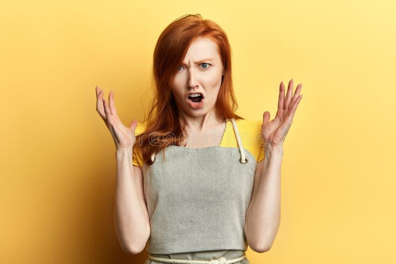 La ragazza frustrata emozionale in grembiule esprime le sue emozioni negative fotografie stock libere da diritti