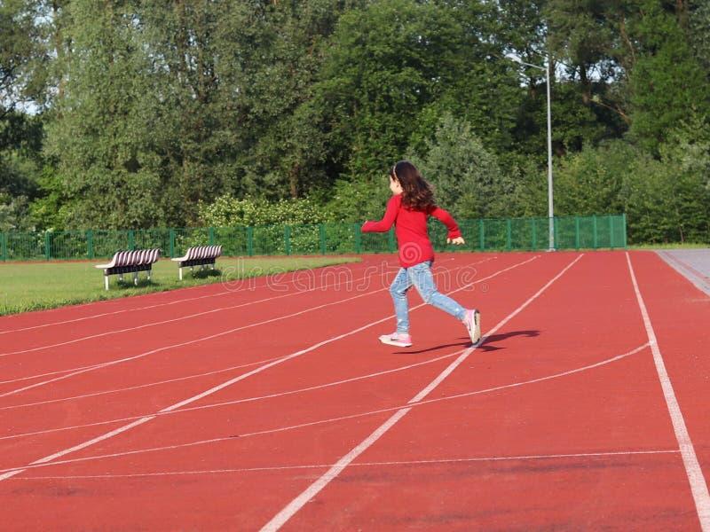 La ragazza funziona attraverso una pedana mobile allo stadio Rivestimento artificiale per correre e gli eventi sportivi Sport e a immagini stock libere da diritti