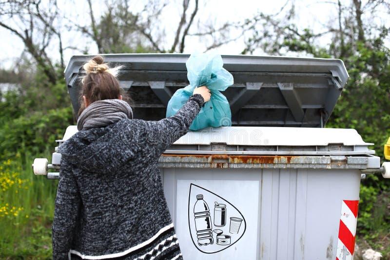 La ragazza getta la borsa con la plastica in un contenitore di rifiuti fotografia stock libera da diritti