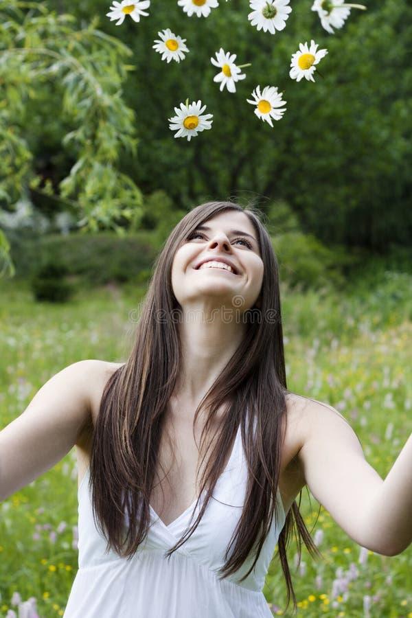 La ragazza getta i fiori nell'aria fotografia stock