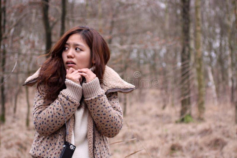 La ragazza giapponese attraente ha spaventato in una foresta scura immagini stock libere da diritti
