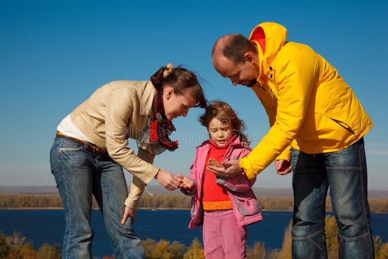 La ragazza gioca con la natura dei genitori in giorno di autunno fotografie stock libere da diritti