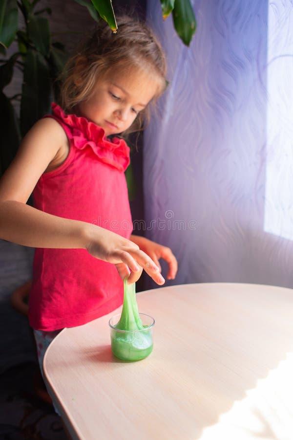 La ragazza gioca con un giocattolo opposto - una melma verde La melma allungata fotografia stock