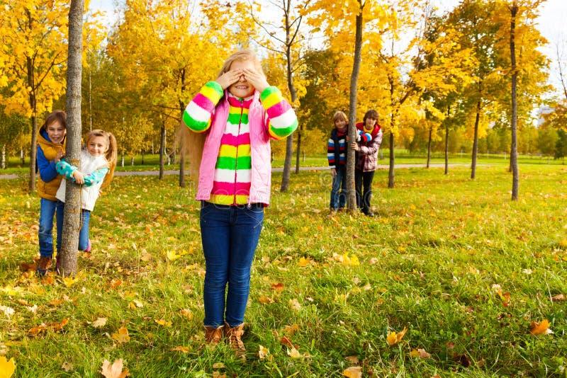 La ragazza gioca a nascondino con gli amici immagini stock libere da diritti