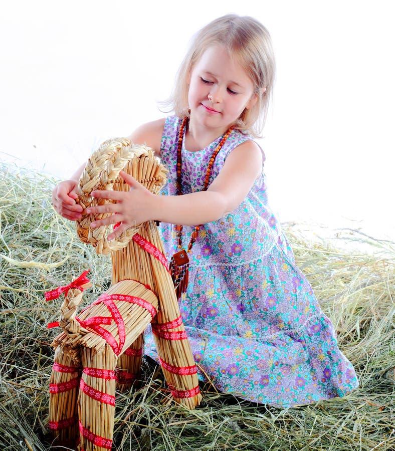 La ragazza gioca nei giochi del fieno con una capra wattled fotografia stock libera da diritti