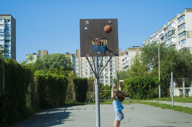 La ragazza gioca la pallacanestro sulla via Getta la palla nel canestro immagini stock libere da diritti