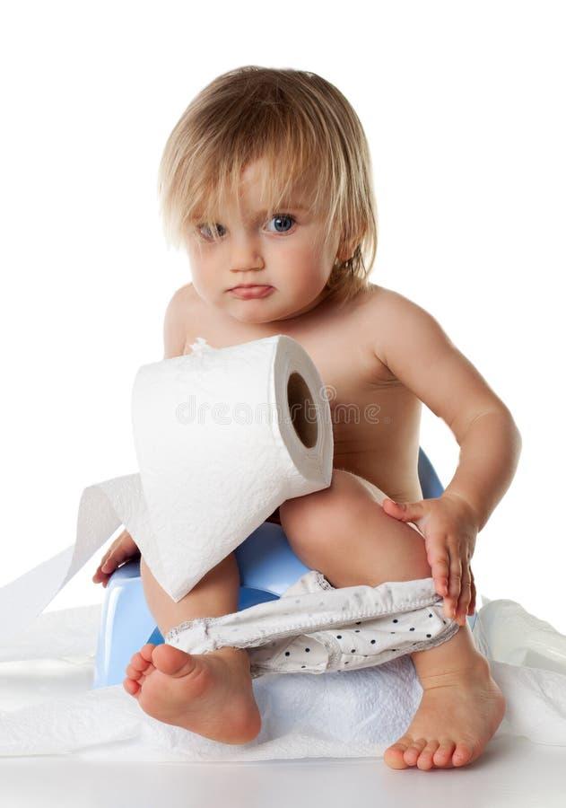 La ragazza gioca sul vaso con la carta igienica immagine stock