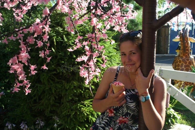 La ragazza gode del sole e dei fiori e mangia il gelato fotografia stock libera da diritti