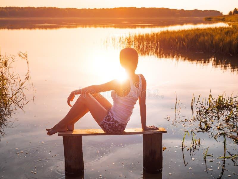 La ragazza gode di bello tramonto che si siede su un banco dal fiume Ragazza che si siede vicino all'acqua all'aperto Lago dorato fotografia stock