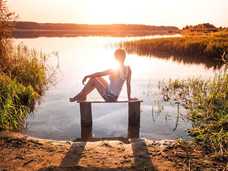 La ragazza gode di bello tramonto che si siede su un banco dal fiume Ragazza che si siede vicino all'acqua all'aperto Lago dorato fotografie stock