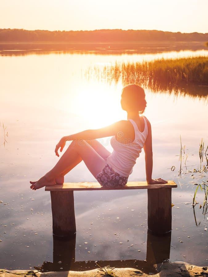 La ragazza gode di bello tramonto che si siede su un banco dal fiume Ragazza che si siede vicino all'acqua all'aperto Lago dorato fotografia stock libera da diritti