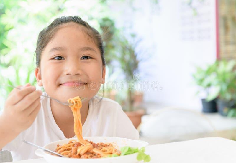 La ragazza gode di di mangiare gli spaghetti con la salsa della carne di maiale fotografia stock libera da diritti