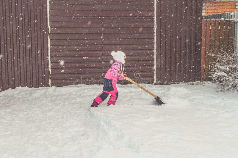 La ragazza, grande pala del bambino rimuove la neve dal percorso nel cortile al garage immagini stock libere da diritti