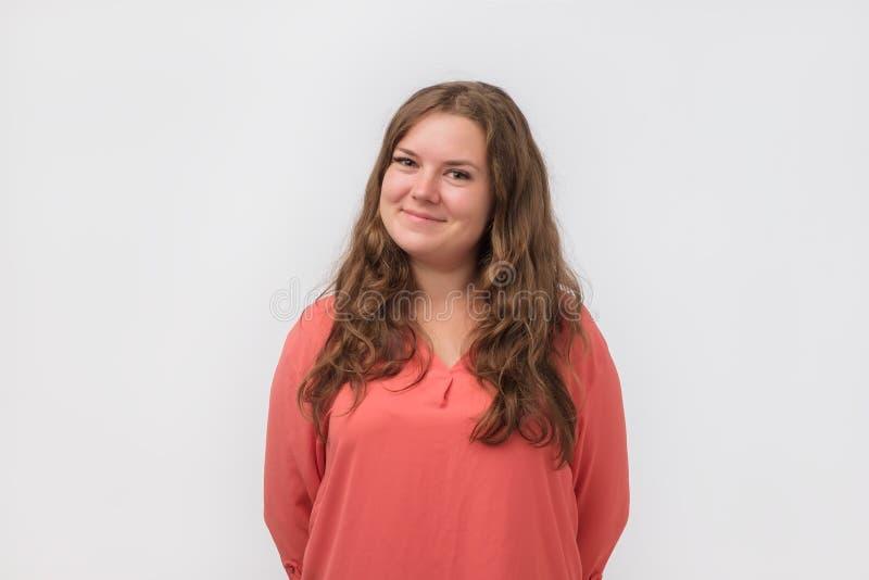 La ragazza grassottella caucasica sorridente con naturale compone in camicia rossa che esamina la macchina fotografica Sta godend fotografie stock libere da diritti