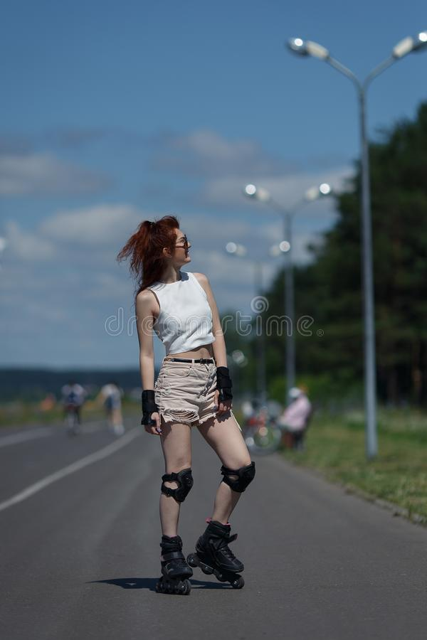 La ragazza graziosa in breve e le cime pattina sui pattini di rullo sulla strada il giorno soleggiato caldo fotografie stock