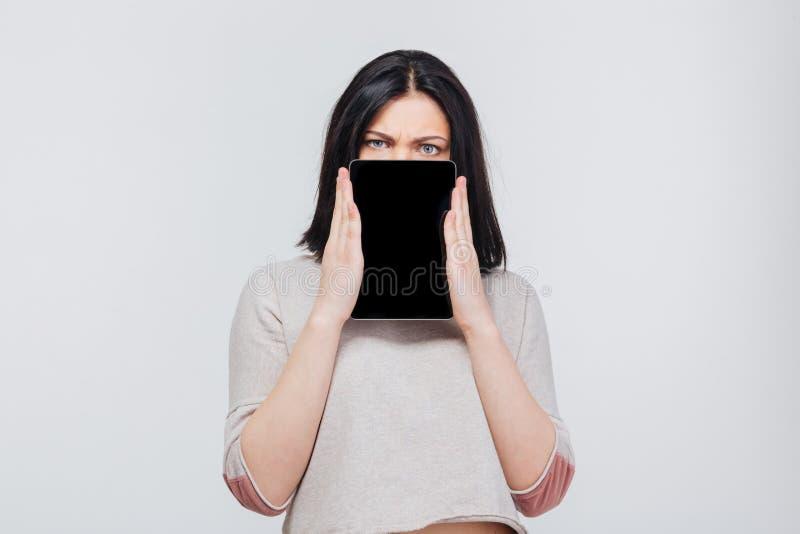 La ragazza graziosa castana copre il suo fronte di pc della compressa immagine stock