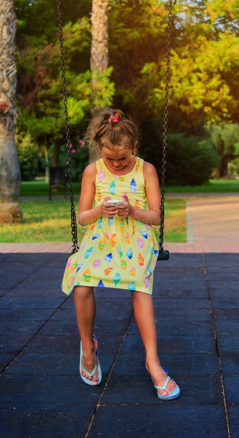 La ragazza graziosa che gioca lo smartphone che si siede sulla catena oscilla sul campo da giuoco del bambino nel parco Tutta l's immagine stock libera da diritti