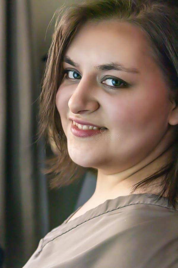 La ragazza graziosa con i bei occhi esamina lateralmente la macchina fotografica fotografia stock