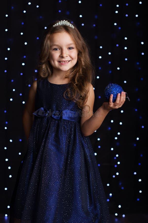 La ragazza graziosa del bambino sta tenendo la palla blu di natale fotografia stock