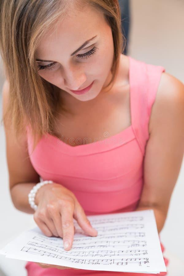 La ragazza graziosa del musicista sta leggendo immagini stock